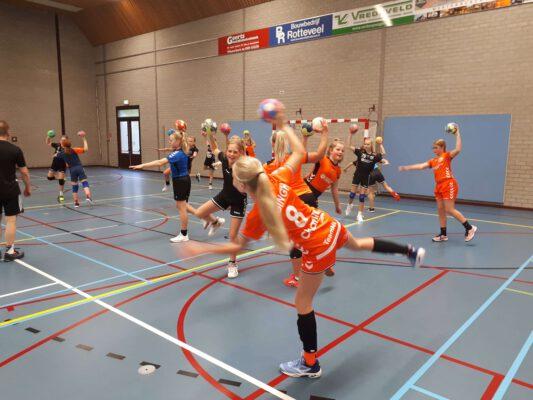 Afbeelding training handbalschool Midden-Drenthe speelsters doen een oefening